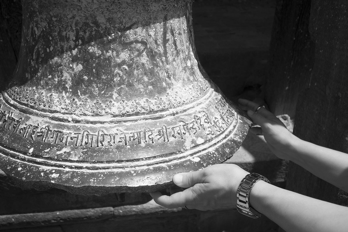 Big Newari Bronze Bell, Cradled by a Man's Hands.