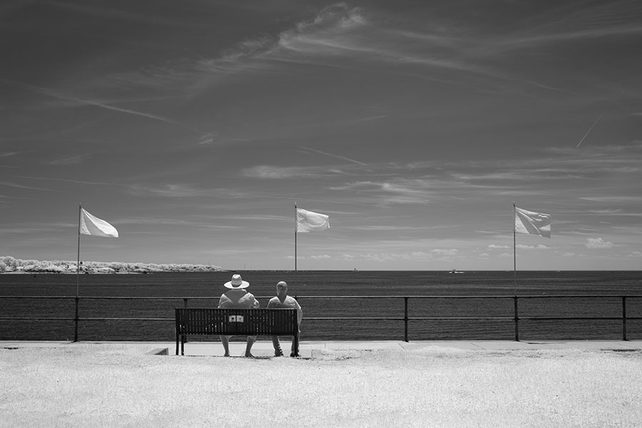 Infrared Photo of Two Men on a Park Bench Overlooking the Outer Harbor of Gloucester, Massachusetts.