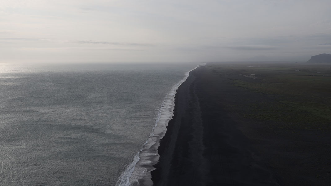 Moody Icelandic Photograph Showing a Diagonal Surf Line Center with Ocean to the Left and Black Sand Beach to the Right.
