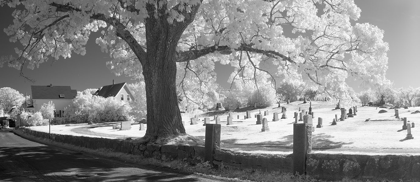 Infrared Panoramic Photo of a New England Cemetary Behing a Stone Wall.