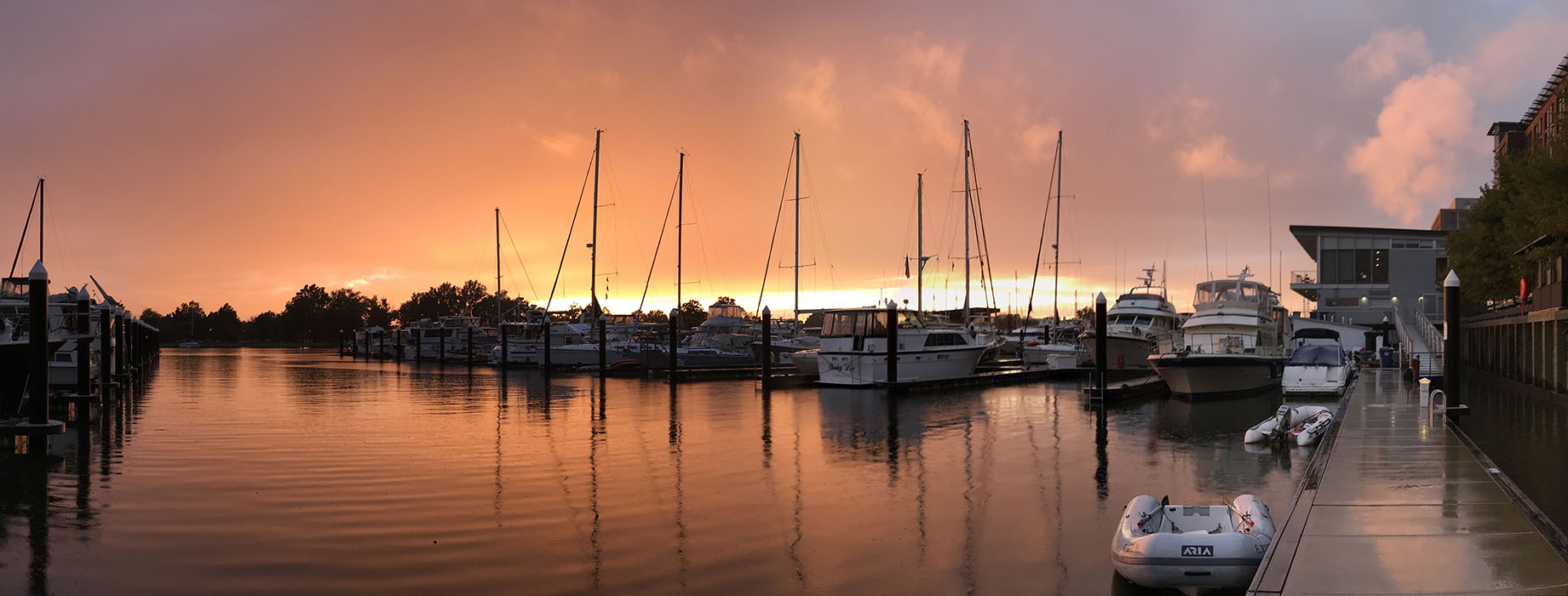 Panorama Red Sunset behind moored boats at yacht basin.