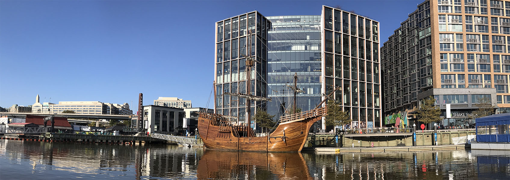 Photo of Replica Santa Maria Sailing Ship Visiting the Washington DC Waterfront with Modern Buildings in Background.