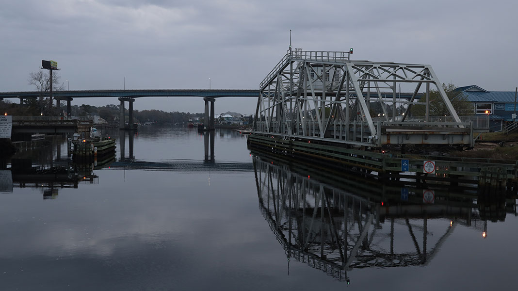 Swing truss bridge over a small body of water.