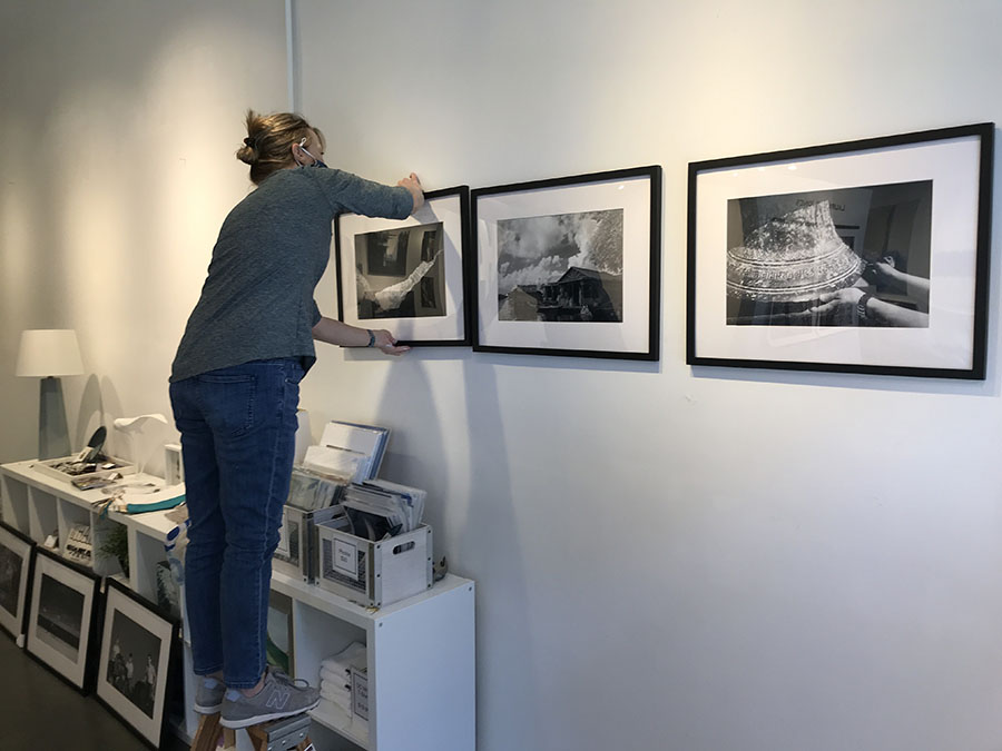 Martha Spak Hanging Photos in a Gallery.