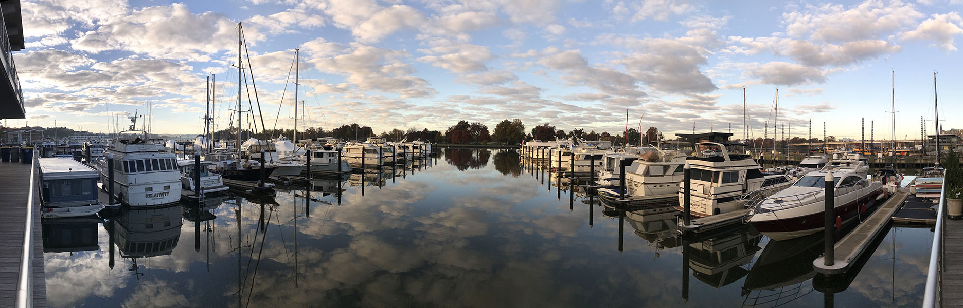 180 Degree views of Marina with Blue Sky and Puffy Clouds Reflected in the Water.